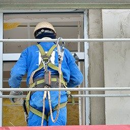 Worker wearing a harness in scaffolding