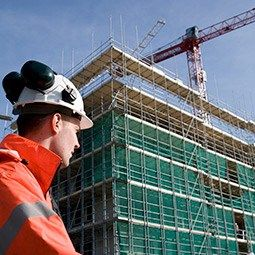 Worker with headphones in the foreground and building with scaffolding in the background